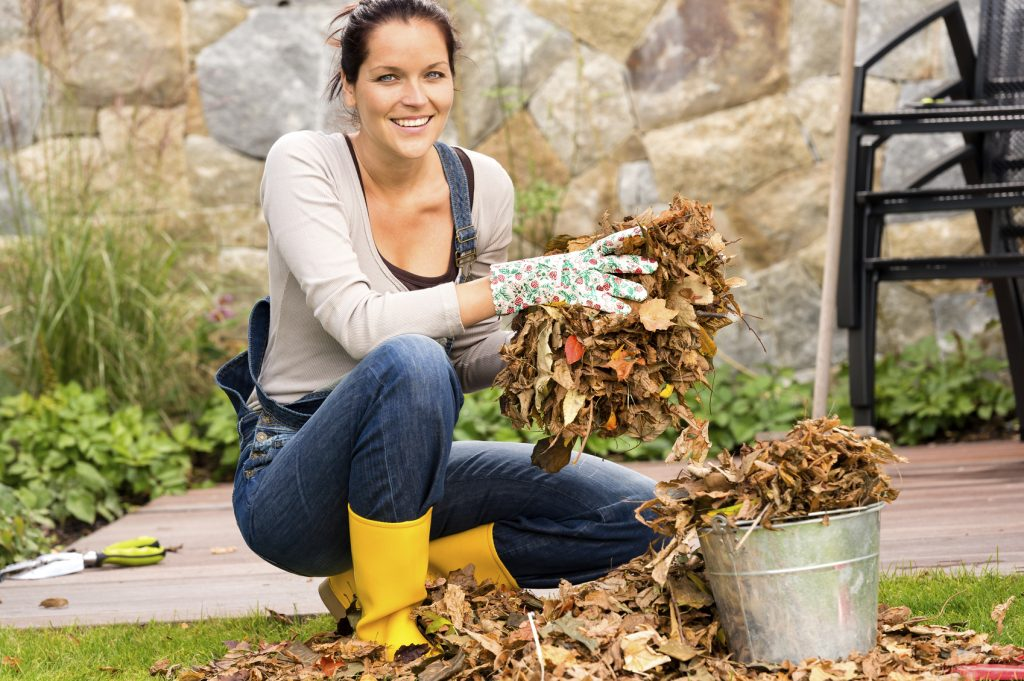 Woman putting leaves gardening cleaning bucket housework