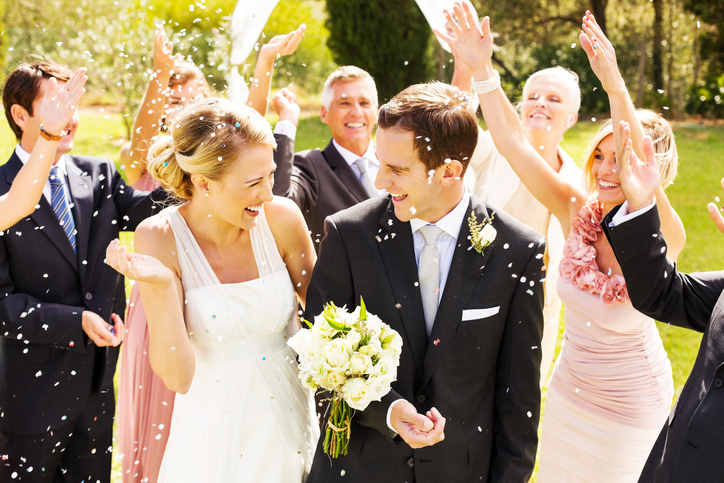 Happy Wedding Guests Throwing Confetti On Couple During Reception In Garden Horizontal Shot